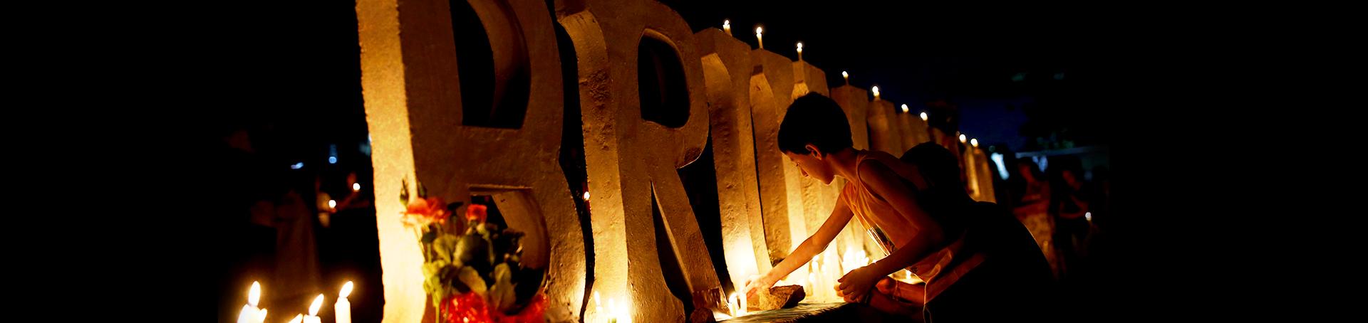 Fotos das letras de Brumadinho com velas e rosas em volta