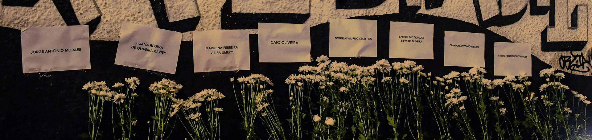 Parede com flores e nomes das vítimas